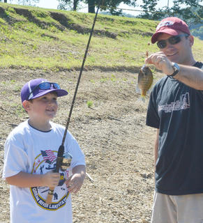 Ethan Garrison, 6, of Campbellsville, caught his first fish on Saturday, with some help from his father, Dr. Shane Garrison.