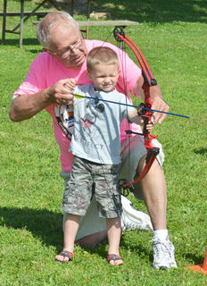 David Bell of Mt. Roberts Baptist Church's On Target for Christ archery ministry helps Landon Craig, 3, of Lebanon, take aim.