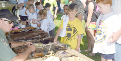 Children learn about animals at the Kentucky Fish & Wildlife booth from Conservation Officer Brandon Boone.