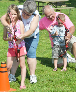 Roberta Walker, at left, and David Bell of Mt. Roberts Baptist Church's On Target for Christ archery ministry help Linsey Craig, 7, and Landon Craig, 3, both of Lebanon, take aim.