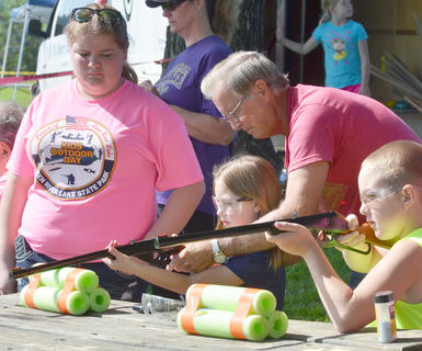 Greg McNear of Campbellsville helps his grandchildren Mallie McNear, 7, and Kaden McNear, 11, take aim with these pellet guns. At left is Kids Outdoor Day volunteer Cheyan Brock.