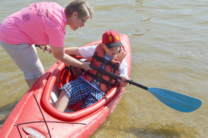 Susan Wise of Campbellsville helps John Michael Phillips, 8, of Campbellsville, learn to paddle a kayak.
