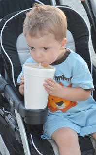 Noah Whitley, 22 months, of Campbellsville, takes a bite of a hot dog at the fair on Friday night.