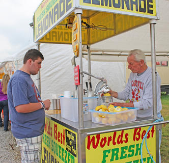 "Lew Edwards makes a cup of the ""World's Best Fresh Squeezed Lemonade"" for Elijah Epperson."