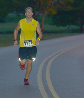 Adam Womack makes sure he glows in the dark as he finishes the race.