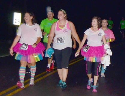From left, Lori Brewster, Jessica Grinnell and Brenda Goode dress the part as they near the finish line.