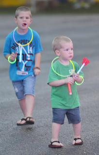 Brady Cook, 5, at left, and his brother, Bentley, 2, glow in the dark as they dance to the music while their mother, Kim, runs the race.