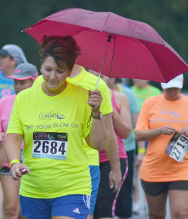 Christy Carpenter holds an umbrella to keep dry as the race gets under way.