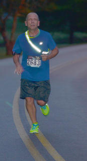 Gary Tucker glows in the dark as he finishes the race.
