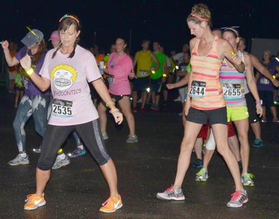 From left, Jessica VanArsdale, Stacie Lay and Rhonda Schnieder lead a dance after they finish the race.
