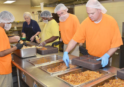 Inmates prepare lunch trays for those serving time at the detention center. Inmates spend their time doing many jobs at the jail, from laundry to serving lunch to cleaning.
