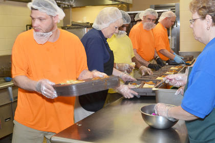 Inmate stack lunch trays to prepare serving their afternoon meal. Inmates spend their time doing many jobs at the jail, from laundry to serving lunch to cleaning.