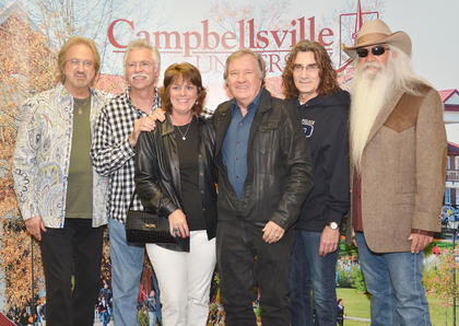 Buzz Cason, nationally known singer and songwriter, and his wife, Peggy, pose for a photo with The Oak Ridge Boys during a meet and greet before Monday's concert.