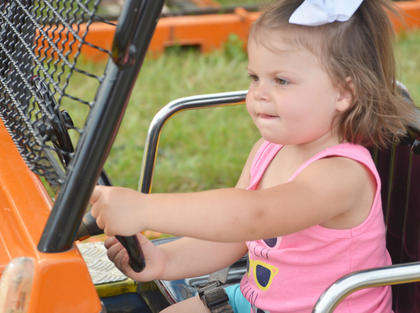 Clara Myers, 1 1/2, of Campbellsville, drives a dump truck on the Kids at Work ride at the fair.