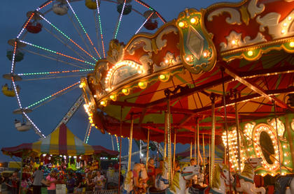 As the sun sets at the fair, the rides illuminate the sky instead.