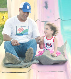 Kirby Smith of Campbellsville holds his daughter Karsyn's hand as they drop down the slide together.