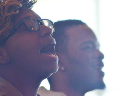 Sarah Porter and Travis Risvy sing along with the Bethel AME Choir during Sunday's MLK worship service.