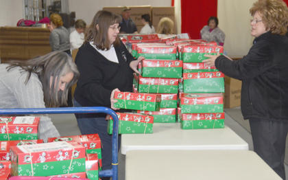 From left, Amy Anderson, Dr. Marilyn Goodwin and Sheri Taylor sort through OCC shoeboxes.