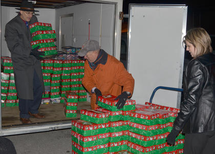 From left, Dr. John Hurtgen, Larry Bowen and Jennifer Lauer carry in the more than 400 shoeboxes donated by the Campbellsville Baptist Church congregation.