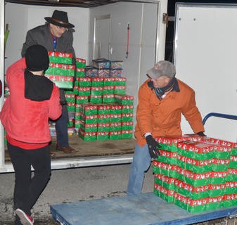 Volunteers carry in the more than 400 shoeboxes donated by the Campbellsville Baptist Church congregation.