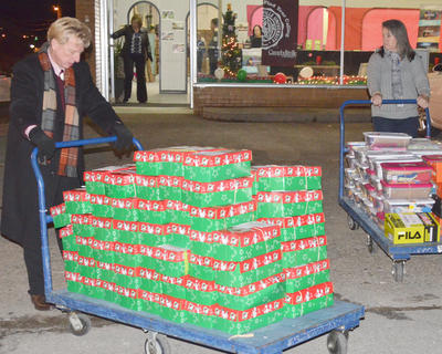 Dr. Ted Taylor, at left, and Amy Anderson take carts of the more than 400 shoeboxes donated by the Campbellsville Baptist Church congregation into the relay station for sorting.