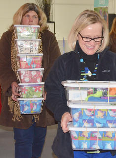 Pam Tennant, at left, and Mary Ann Rice carry OCC boxes to be packed and taken to Boone, N.C., for final sorting before being shipped worldwide.