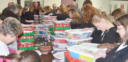 Volunteers place their hands on the OCC boxes donated and pray for the children who will receive them.