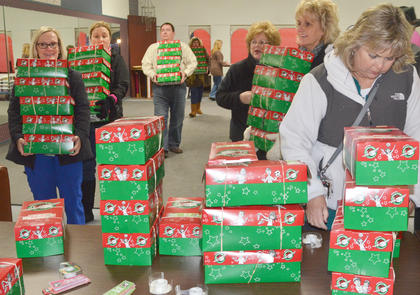 Volunteers carry OCC shoeboxes to be sorted.