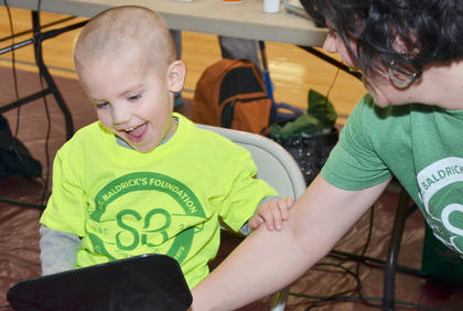 Owen Skaggs, 4, smiles as he sees his bald head. His mother, Chrissy, shaved his head.