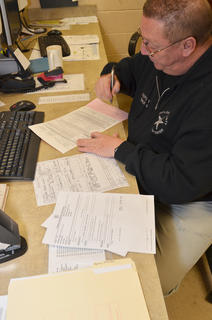 Booking Officer J.W. Maupin completes paperwork as an inmate is being released from custody.