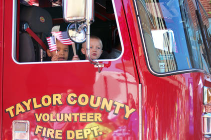 Children wave flags while riding in a Taylor County Fire & Rescue fire truck.