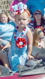 Maria Burton, who was named Miss Taylor County Fair Toddler, rides in the Fourth of July parade on Friday morning.