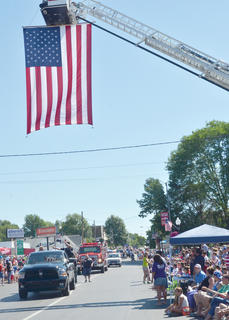 Campbellsville Fire & Rescue's large American flag waves as the annual Fourth of July parade gets underway on Friday morning.
