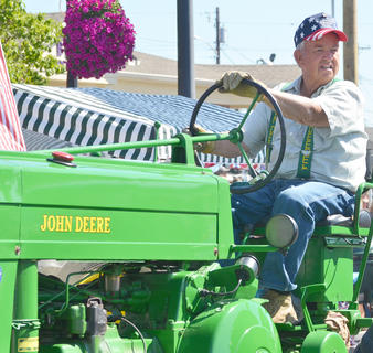Wayne Livesay rides atop his tractor in the Fourth of July parade on Friday morning.