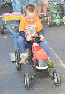 Drayden Clifton, 4, of Campbellsville, tries his hardest to pedal this tractor at the Kentucky Farm Bureau booth on Main Street.