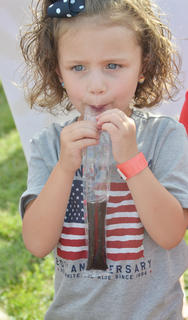 River Miller, 4, of Campbellsville, takes a big bite of a grape Popsicle at the Family Fun Zone.