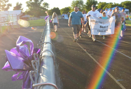 Above, Amazon.com team members make their way around the Taylor County High School track during the Relay for Life team lap on Friday night. Purple bows, like the one at left, have been seen hanging around Taylor County in honor of Relay for Life.