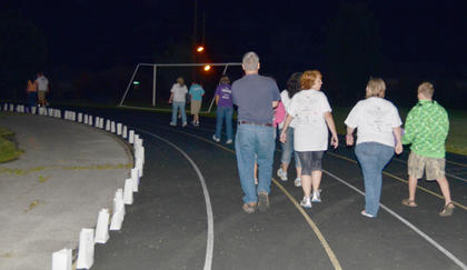 Residents make their way around the TCHS track for a silent lap to honor those names read during the luminary ceremony.