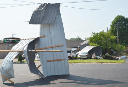 A roof on Magnolia Alley's storage building was blown away during Thursday's storm and ended up caught in a power line. Part of the roof traveled across the street and damaged a home.