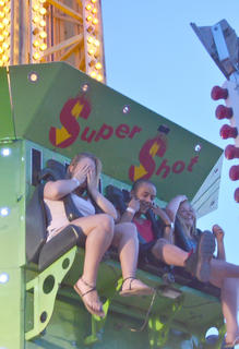 Fairgoers hold on tight while riding the Super Shot.
