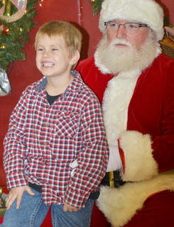 James Ramsey, 6, a kindergartener at TCES, smiles as he poses for a photo with Santa.