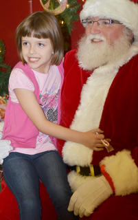 Alora Whitlock, 7, a second-grader at TCES, gives Santa a hug as she poses for a photo with him.