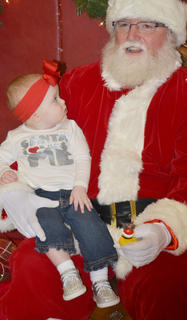 Avery Arnold, who will celebrate her first birthday on Dec. 27, takes a good look at Santa as she sits in his lap.