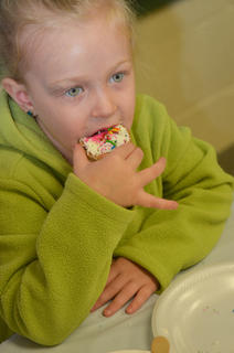 Chesney Davis, 6, a first-grader, takes a bite of the cookie she decorated.