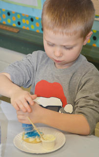 Tray Parish, 5, a pre-kindergarten student, decorates his cookie with blue sprinkles.