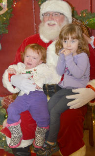 Rose Didonato, 3, at right, is content in Santa's lap, but her sister, Ivy, 18 months, isn't quite sure about him.