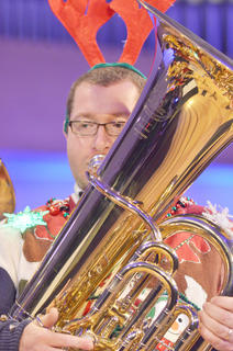 "A tuba ensemble performs ""Rudolph the Red-Nosed Reindeer,"" led by Stephen Bishop, director of the Taylor County High School Marching Band. Above, Bishop dresses the part in a Christmas sweater complete with twinkling lights."