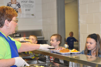 Taylor County Elementary School cafeteria employee Joyce Russell serves lunch to Students Isaiah White, Michael Baker and Reagan Sultzbach.