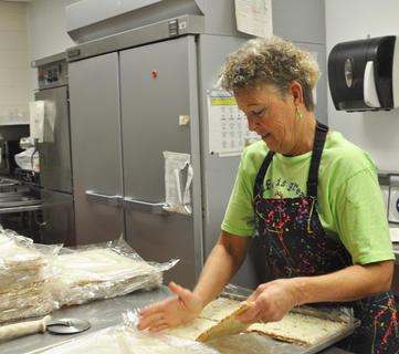 Taylor County Elementary School cafeteria employee June Carney breaks cheese pizza squares apart before placing them in the oven.
