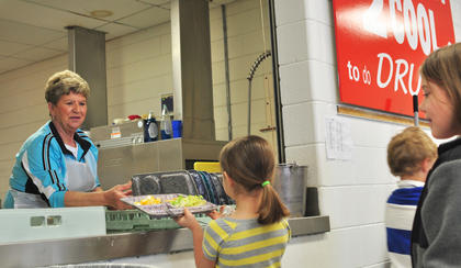 Taylor County Elementary School cafeteria employee June Carney collects a lunch tray from a student.